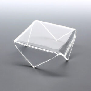 Clear acrylic display riser with pointed corner folds for displaying items