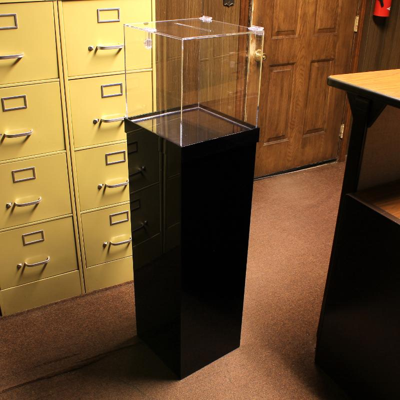 Clear acrylic donation box on top of a black pedestal display riser